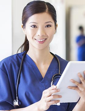 Portrait Asian Chinese female clinical hospital nurse in scrubs using wireless tablet at modern medical center