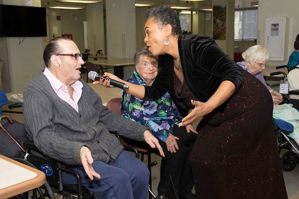 Entertainer holding a microphone, and signing with senior resident.
