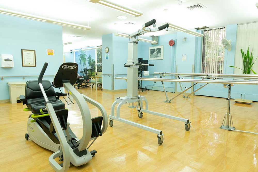 Room filled with exercise and rehab equipment at Downtown Brooklyn Nursing and Rehabilitation Center.