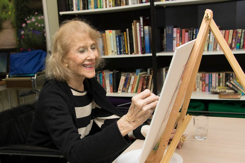 Senior woman smiling while painting on canvas.