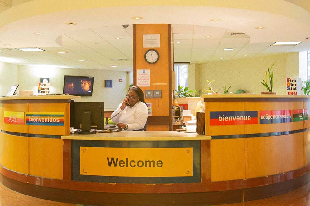 Admissions desk at Downtown Brooklyn Nursing and Rehabilitation Center, welcome signs in multiple languages.